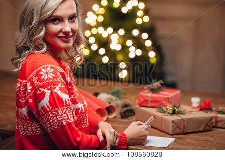 blonde woman  write on christmas postcard