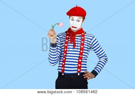 Mime with flower.Emotional funny actor wearing sailor suit, red beret posing on blue background.