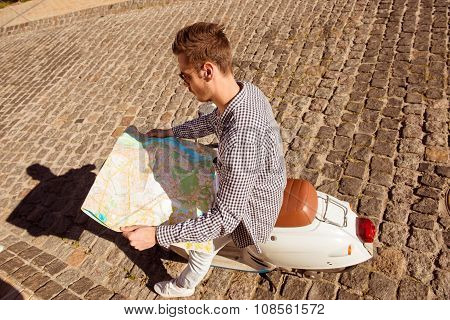 Handsome Man Sitting On The Scooter Searching A Map