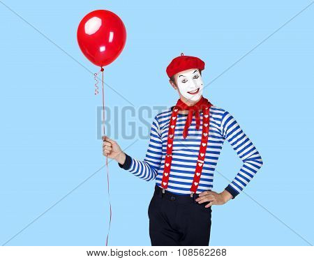 Mime with balloon.Emotional funny actor wearing sailor suit, red beret posing on blue background.