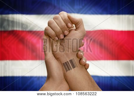 Barcode Id Number On Wrist Of Dark Skinned Person And National Flag On Background - Costa Rica