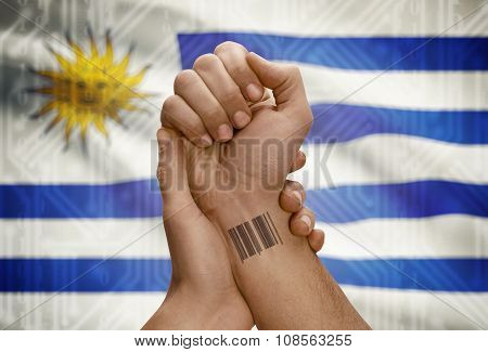 Barcode Id Number On Wrist Of Dark Skinned Person And National Flag On Background - Uruguay