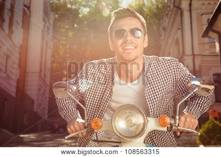 Cheerful Handsome Young Man With Glasses Riding The Motorbike