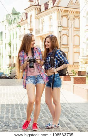 Two Pretty Young Tourists Looking At The Screen Of A Camera And Loughing