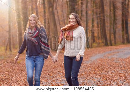 Two Joyful Women Running Through A Park