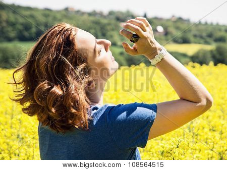 Young Woman In Yellow Rapeseed Field, Sunlight, Rear View