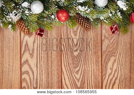 Christmas decor and snow fir tree over wooden background with copy space