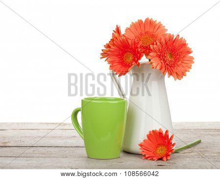 Orange gerbera flowers in pitcher and cup of drink on wooden table. Isolated on white background