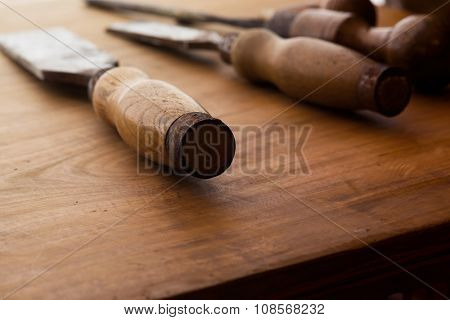 Old and well used wood carving chisels, on a old workbench. Old chisel with an oak handle. Shallow depth of field.