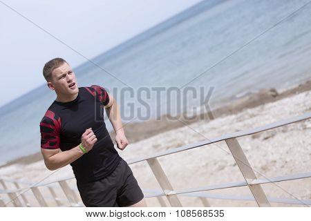 Male Runner Running On The Beach