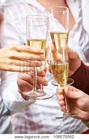 Hands of toasting friends holding flutes with champagne