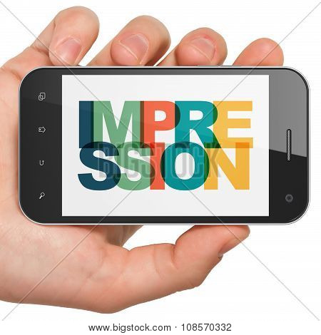 Marketing concept: Hand Holding Smartphone with Impression on  display