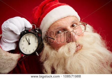 Anxious Santa holding alarm clock by his ear