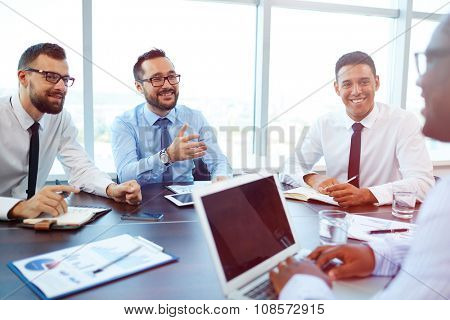 Happy businessmen looking at partner during conversation