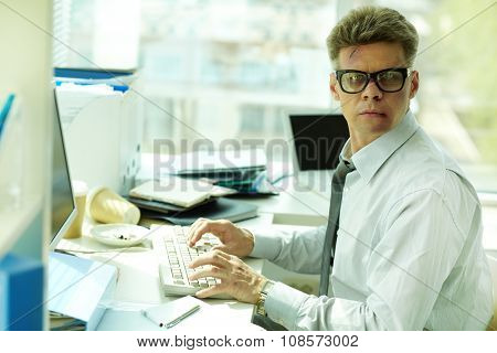 Businessman with bruised face typing at workplace