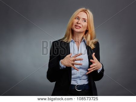 Mature employee in suit gesticulating while explaining something