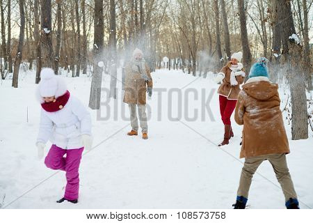 Happy family playing snowballs in winter park