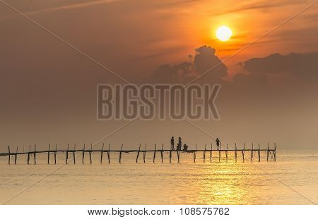 Family welcome sunrise on wooden bridge
