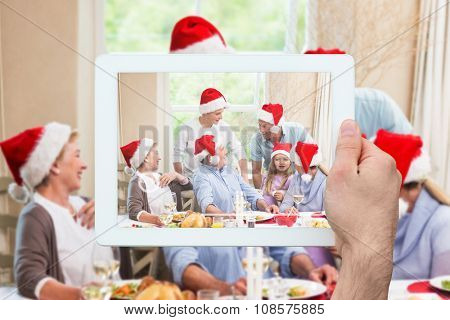 Hand holding tablet pc against happy extended family in santa hat speaking together Happy extended family in santa hat speaking together at home in the living room