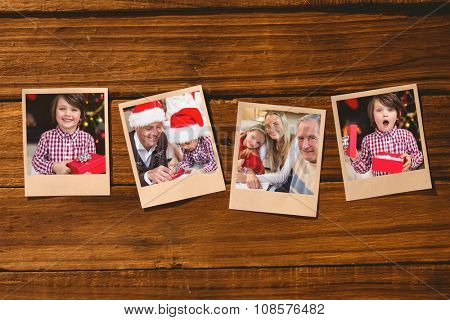 Instant photos on wooden floor against festive little boy holding a gift
