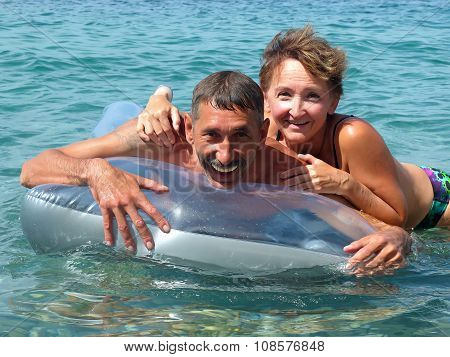 Old couple lying on water mattress