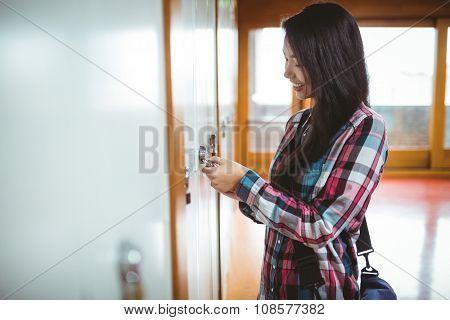 Smiling student opening locker at the university