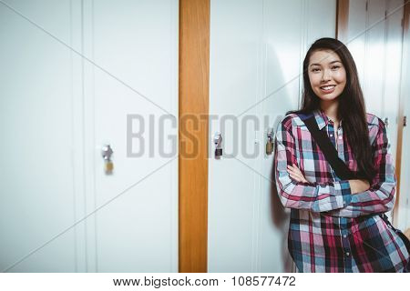 Cheerful student standing next the locker with arms crossed at the university