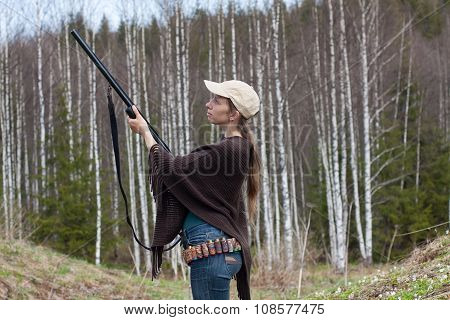 Woman Hunter  Takes Aim From A Gun In The Forest