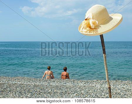 Sea and hat on a stick with two women