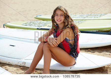 Surfer kid girl sitting in surfboard on the beach sand