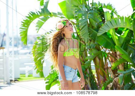 Blond kid girl at banana tree leaves in bright day light in Mediterranean