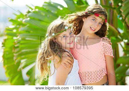 kid girl sisters hug at banana tree leaves in bright day light in Mediterranean