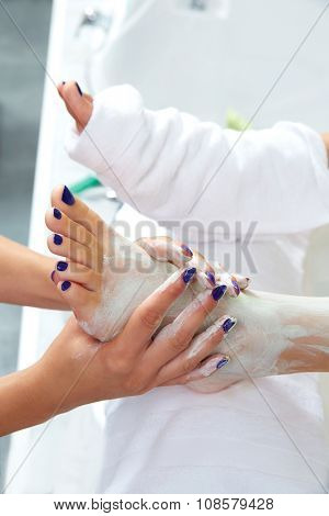 Pedicure applying nourishing moisturizer mask in legs of woman in nails salon