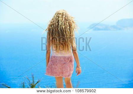 Blond girl looking blue Mediterranean sea as a tourist in Spain rear back view
