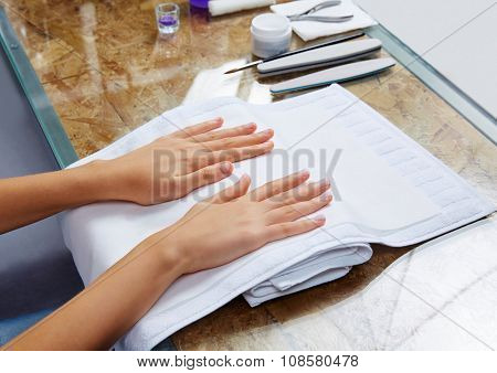 woman hands with nails before treatment on white towel in salon