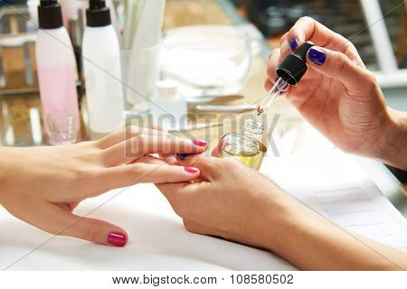 Nails top coat finishing vernis varnish after nail polish in woman hands at salon