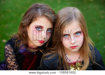 Halloween makeup kid sister girls blue eyes in outdoor backyard lawn