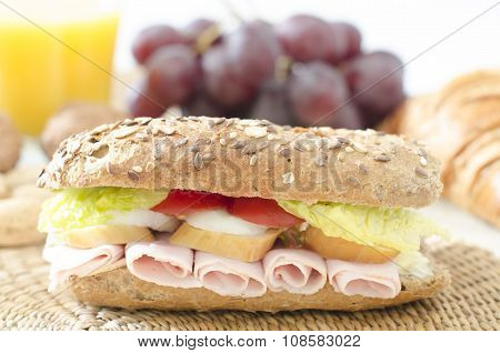 Baguette on a table with croissant, nuts, orange juice, grapes isolated