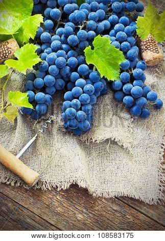 grapes in vintage setting with corks on wooden table