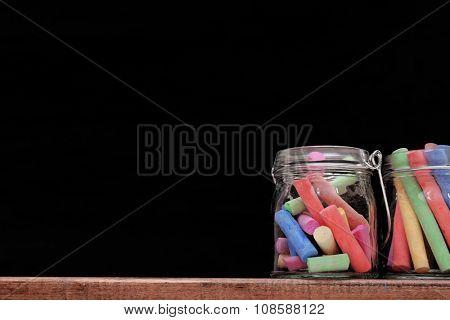 Multicoloured chalk in a jars on blackboard background