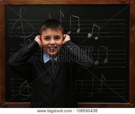 Young cute schoolboy posing at the blackboard with musical notes