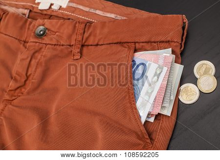 Euro Paper Money Sticking Out Of His Trouser Pocket And A Coin On The Table