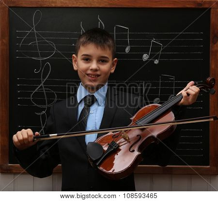 Young cute schoolboy holding the violin at the blackboard with musical notes