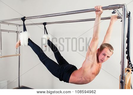 Pilates aerobic instructor man in cadillac fitness exercise