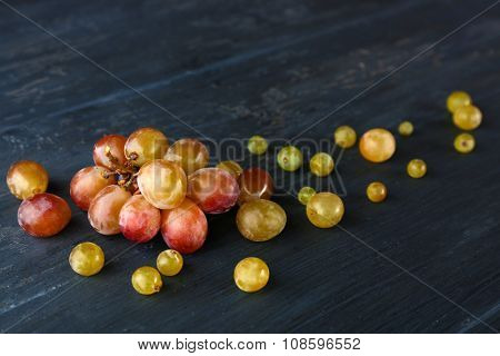 Juicy green and purple grapes, on wooden background