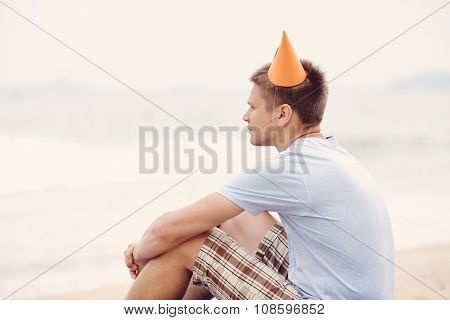 Retro colored side view portrait of young man wearing orange party hat, t-shirt and checkered shorts celebrating birthday sitting with hands on knees on beach near tropical sea - loneliness concept