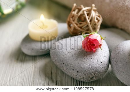 Spa composition of flowers, candles and stones on white wooden background, in spa salon