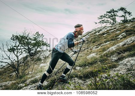 male athlete climbs slope of mountain