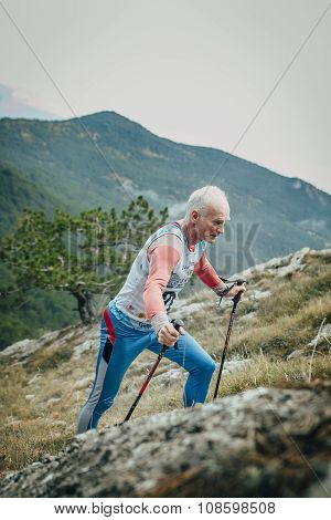 male athlete senior years with walking sticks going uphill