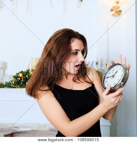 Attractive Smiling Girl Stares At The Clock With Her Mouth Open